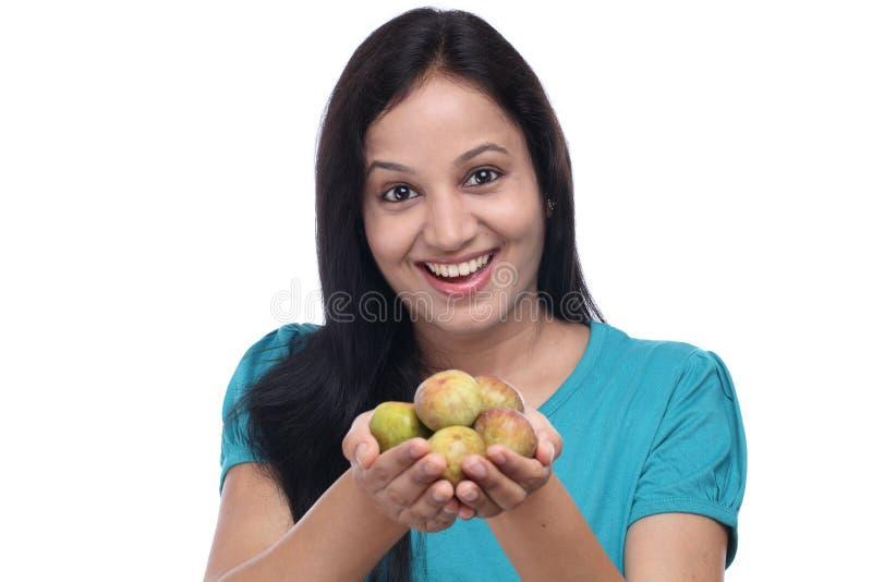 Junge Frau, die Feigenfrucht hält stockfoto