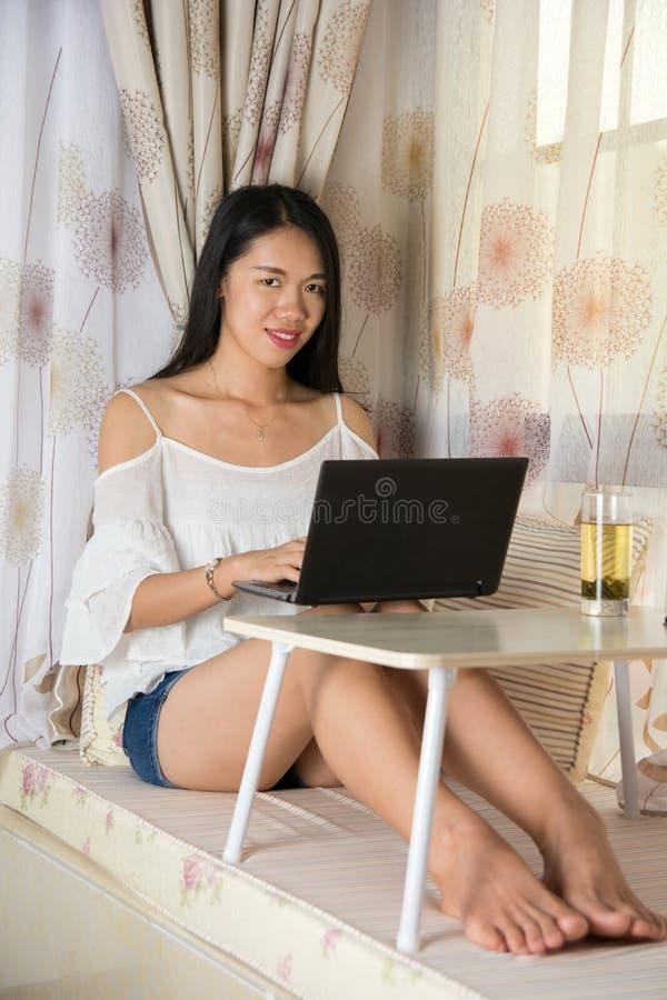 Junge Frau, die am Fenster Schossspitze verwendet lizenzfreie stockfotografie
