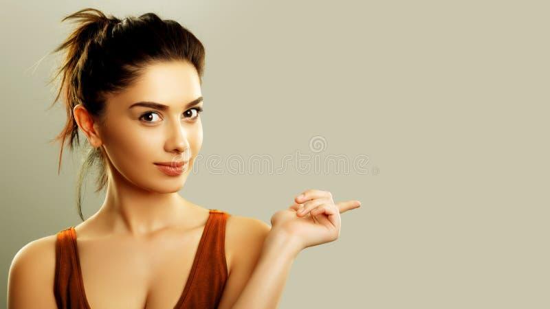 Junge Frau, die Finger auf Kopienraum zeigt stockbild
