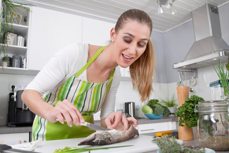 Junge Frau, die Fische in der Küche kocht lizenzfreie stockbilder
