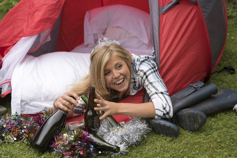 Junge Frau, die Flaschen lacht und hält lizenzfreies stockbild