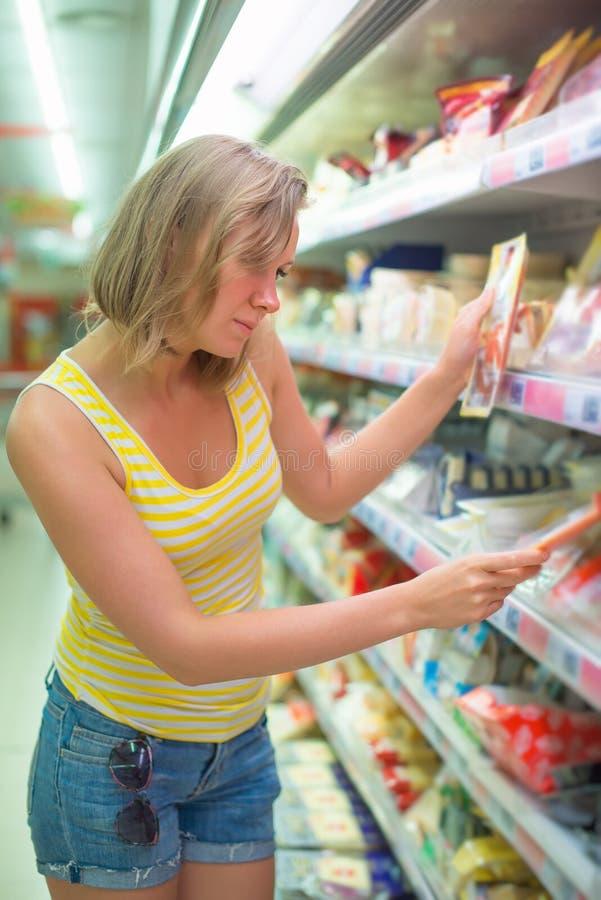Junge Frau, die Fleisch wählt stockfotografie