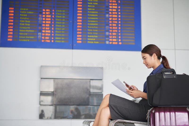 Junge Frau, die in Flughafen wartet lizenzfreie stockfotografie