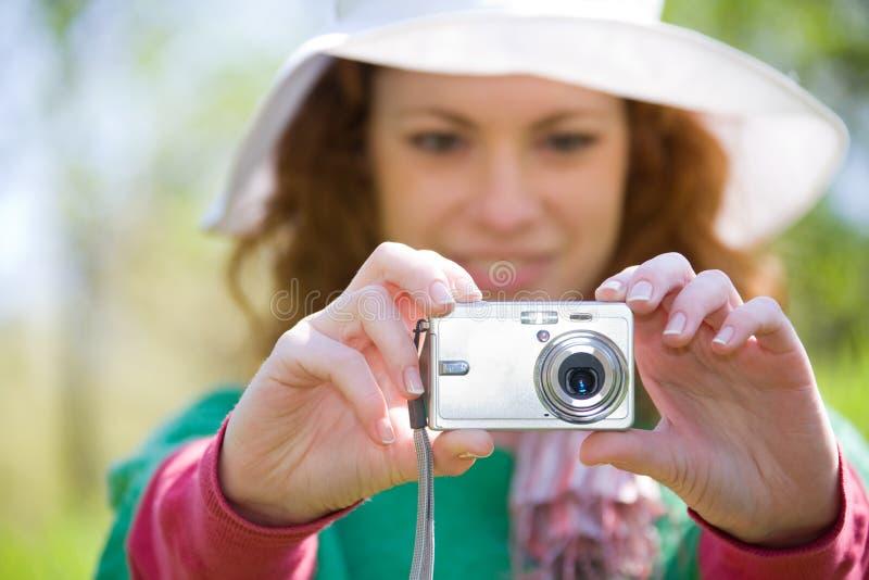 Junge Frau, die Foto mit Digitalkamera macht lizenzfreie stockbilder