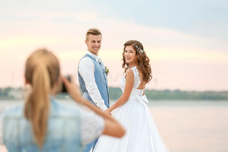 Junge Frau, die Foto von Hochzeitspaaren nahe Fluss, Abschluss aufnimmt lizenzfreie stockfotografie