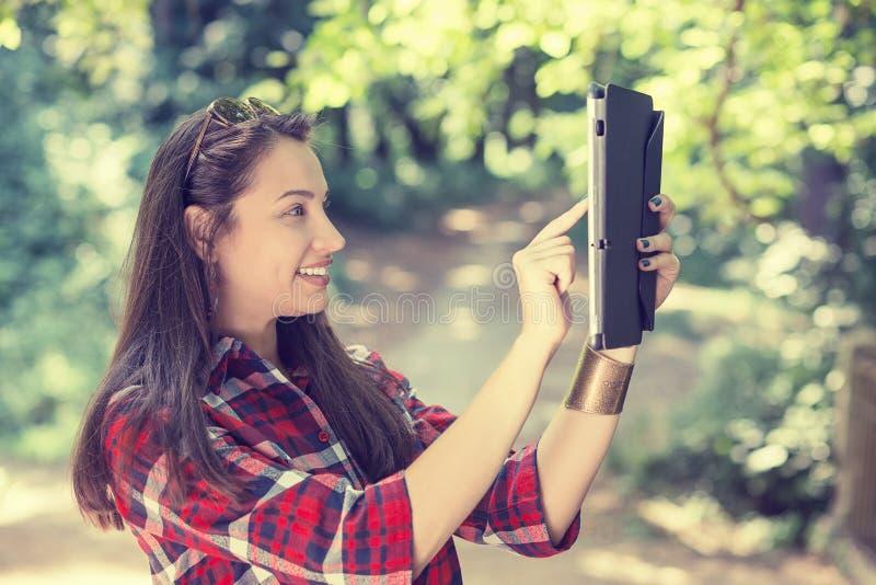 Junge Frau, die Foto von, selfie mit mobilem PC macht stockfotografie
