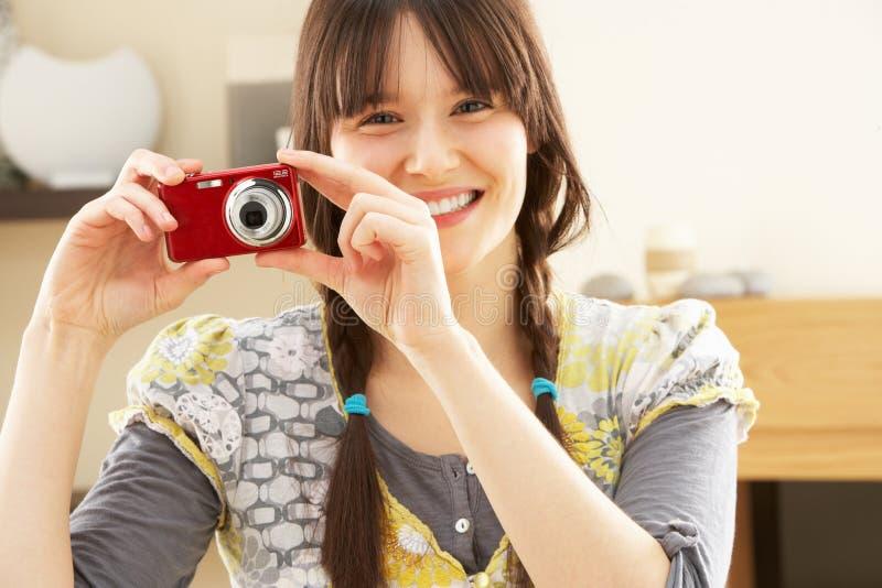 Junge Frau, die Fotographie auf Digitalkamera nimmt lizenzfreie stockfotografie