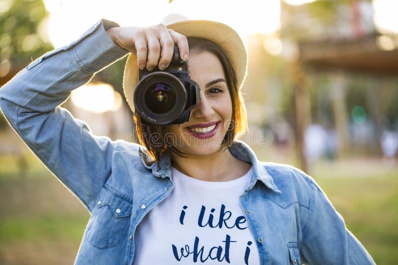 Junge Frau, die Fotos mit Berufskamera an Sommer gre macht lizenzfreie stockfotos