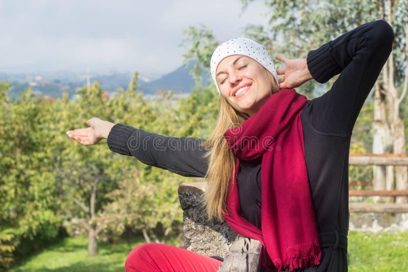 Junge Frau, die frei draußen am Frühlingstag glaubt lizenzfreies stockbild