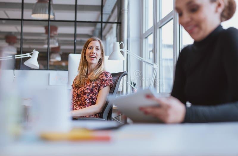 Junge Frau, die freundlichen Chat mit ihrem Kollegen hat stockbilder