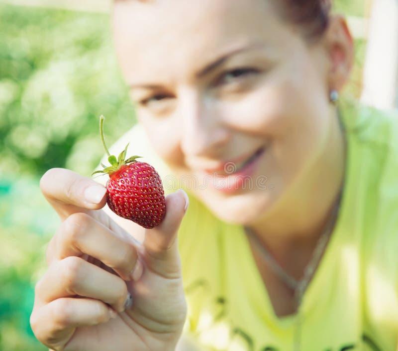 Junge Frau, die frische Erdbeere, Frühlingsgartenthema isst stockfoto