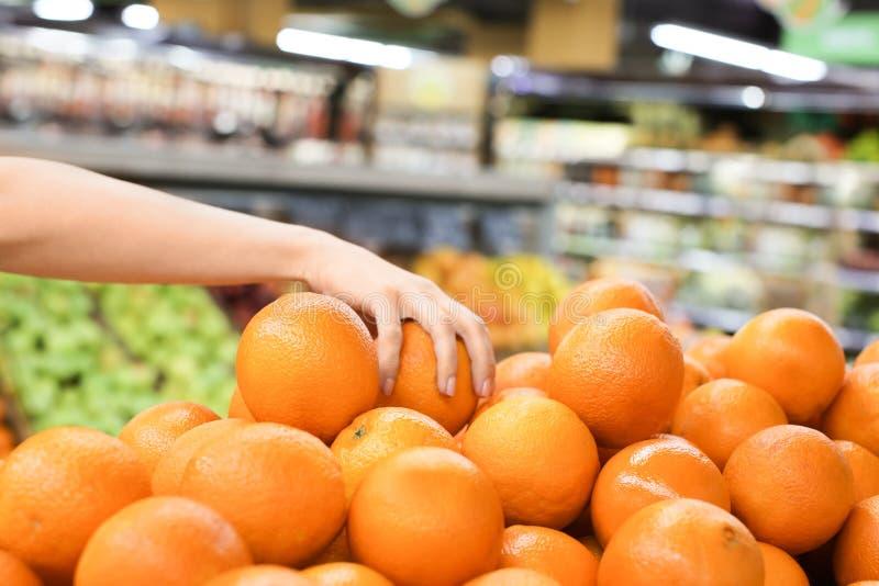 Junge Frau, die frische reife Zitrusfrucht am Markt wählt lizenzfreie stockbilder