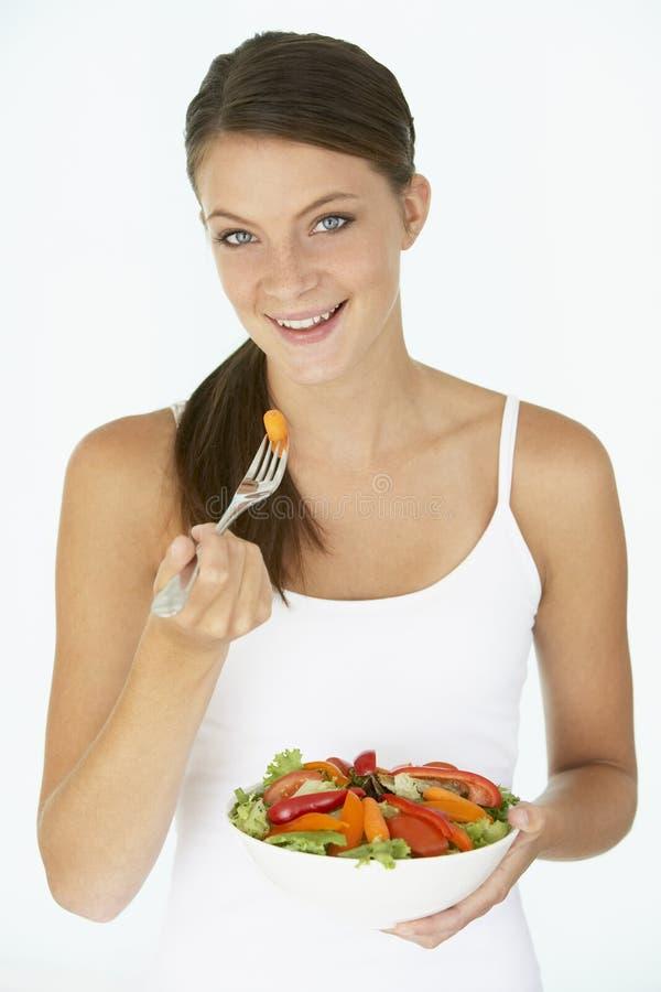 Junge Frau, die frischen Salat isst lizenzfreies stockfoto