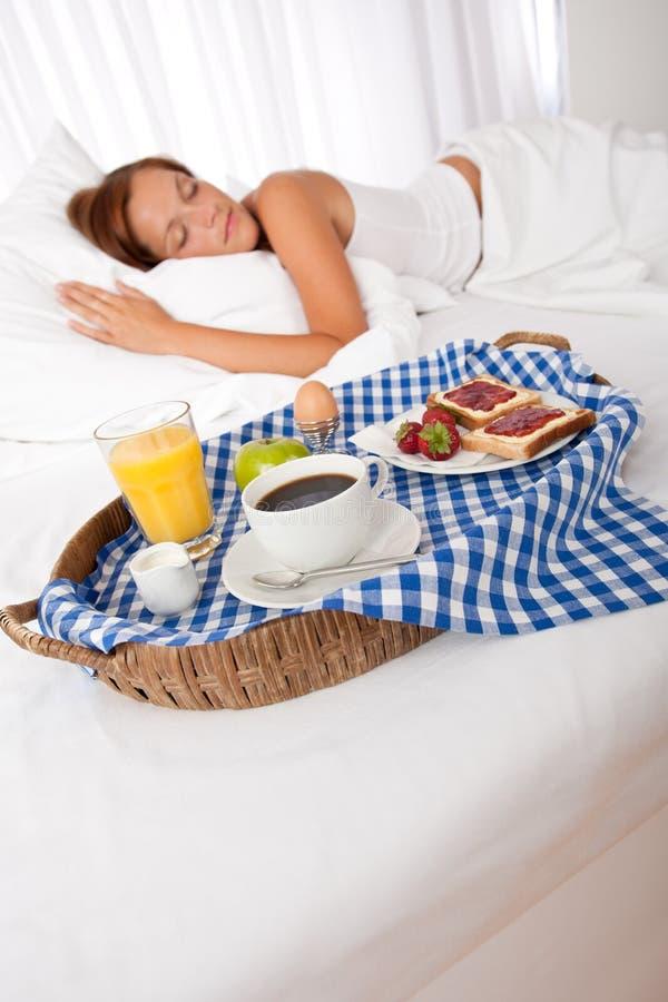 Junge Frau, die gebildetes Haupt frühstückt stockfoto