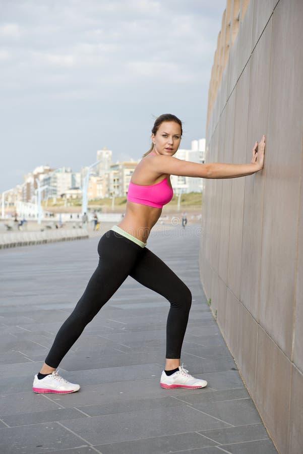 Junge Frau, die gegen eine Granitwand ausdehnt stockfotos