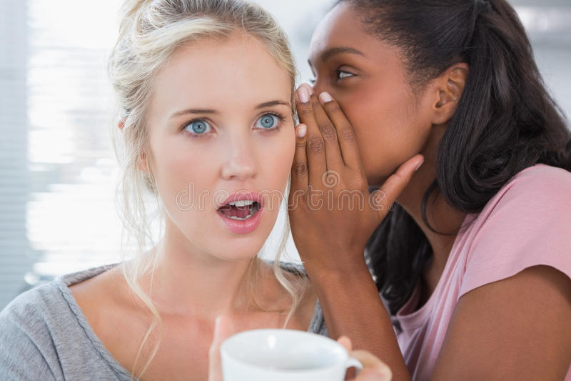 Junge Frau, die Geheimnis zu ihrem Freund flüstert lizenzfreies stockfoto