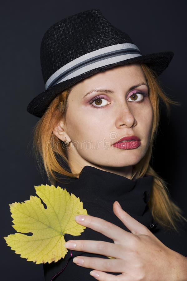 Junge Frau, die gelbes Blatt anhält lizenzfreies stockbild