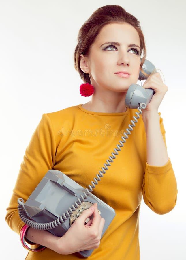 Junge Frau, die gelbes Kleid im Retrostil mit altem Telefon trägt stockfoto