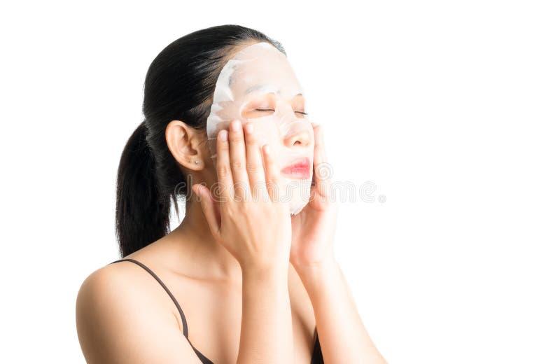 Junge Frau, die Gesichtsmaskenblatt tut stockfotografie