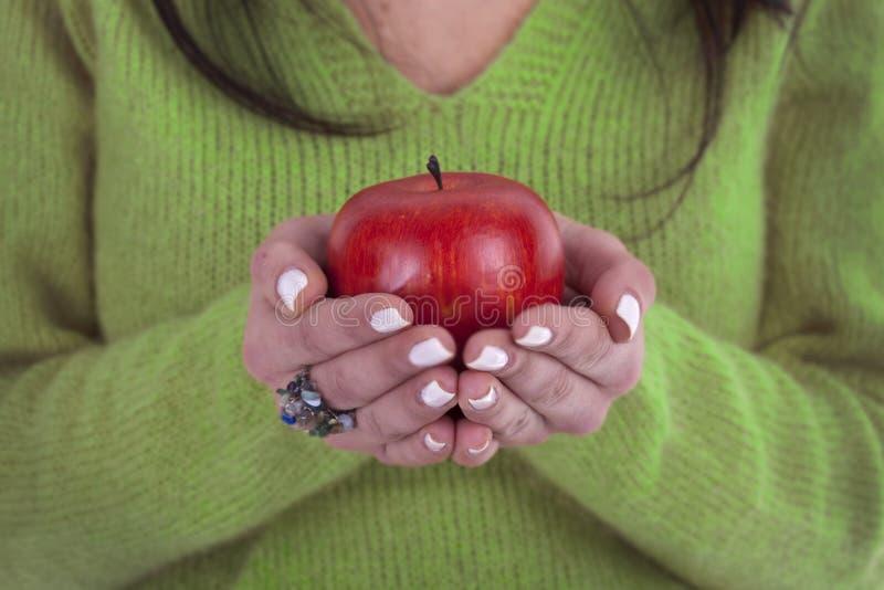 Junge Frau, die gesunden roten Apfel in den Händen anhält stockfotografie
