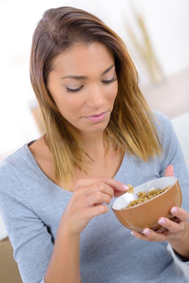 Junge Frau, die Getreidemusselinflocken isst lizenzfreies stockfoto