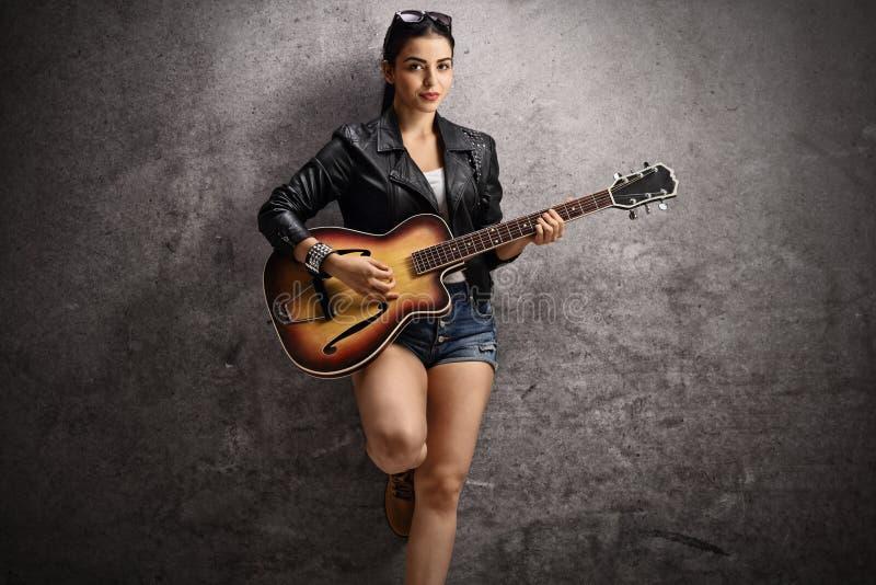Junge Frau, die Gitarre spielt und auf einer rostigen grauen Wand sich lehnt stockbild