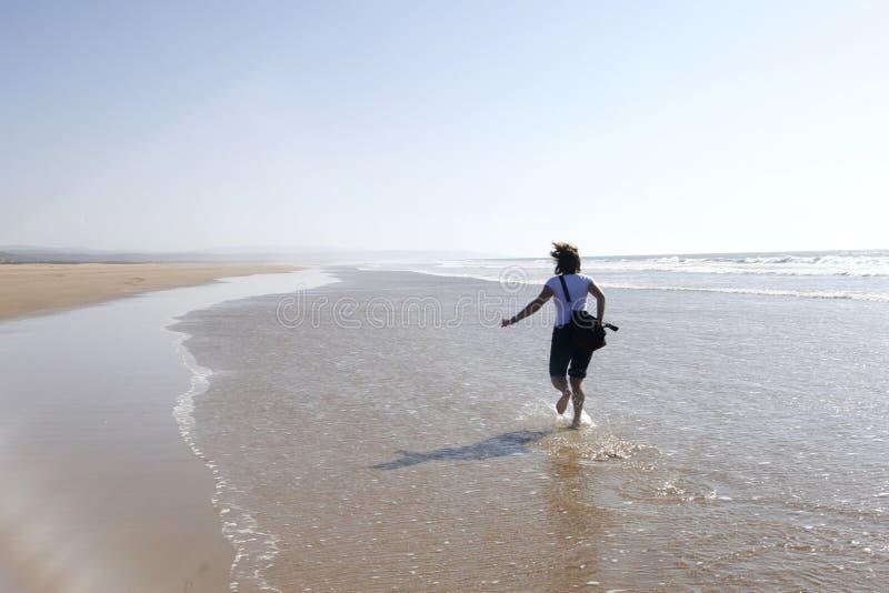 Junge Frau, die glücklich auf einen Strand läuft lizenzfreie stockbilder