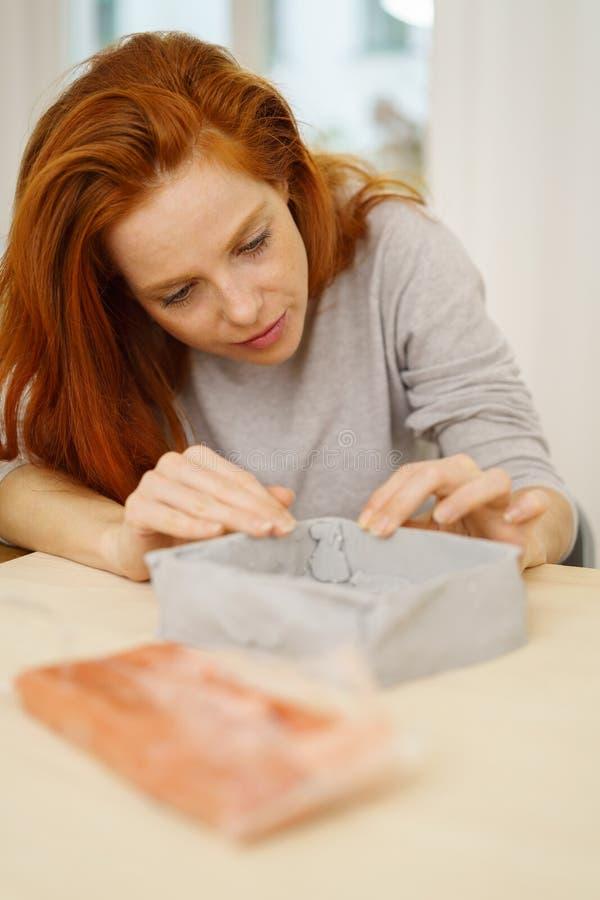 Junge Frau, die grauen Lehm in einen Gegenstand formt stockfotografie