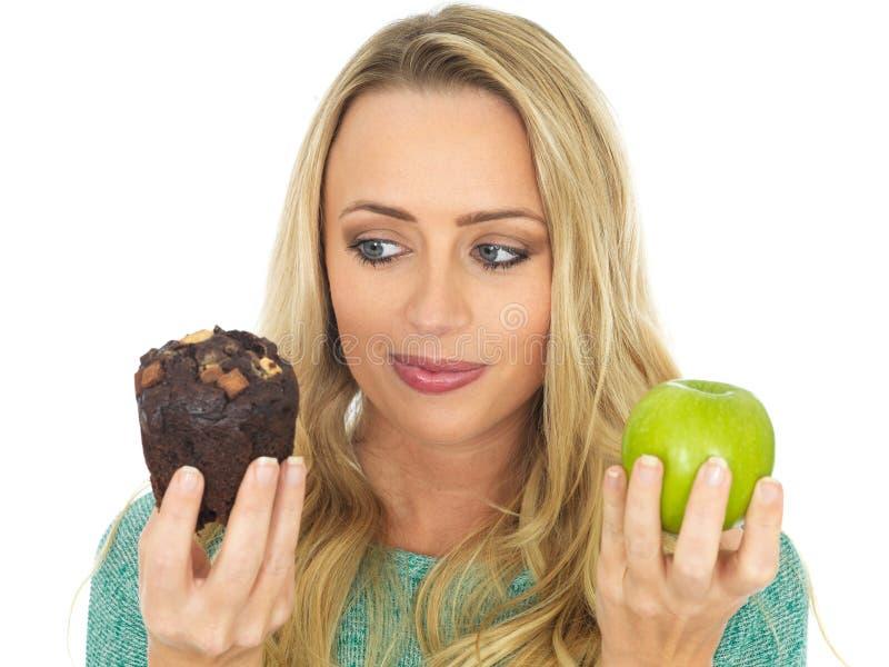 Junge Frau, die gutes und schlechtes Lebensmittel vergleicht lizenzfreies stockfoto