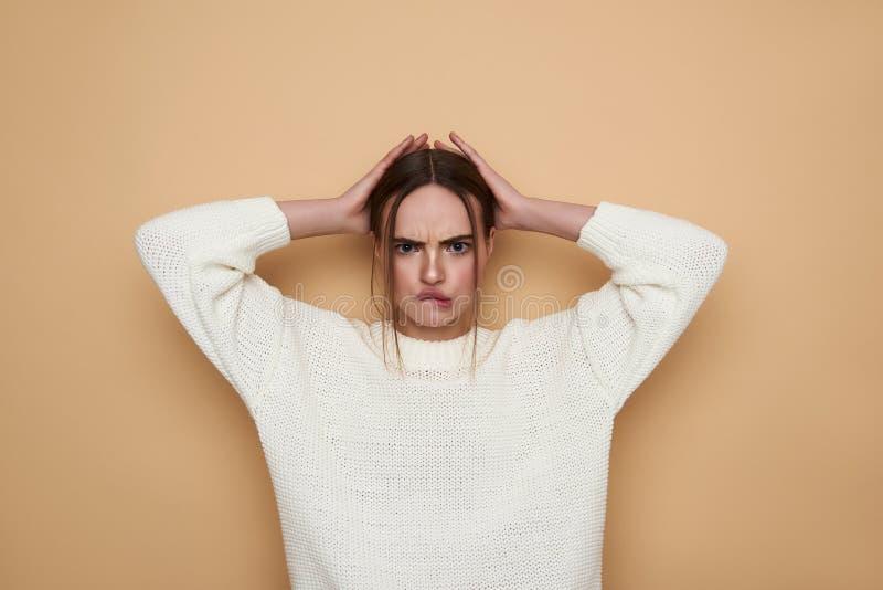 Junge Frau, die H?nde auf ihren Kopf die Stirn runzelt und setzt lizenzfreie stockbilder