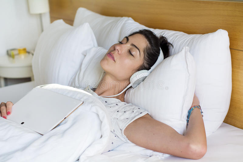 Junge Frau, die in hörender Musik des Betts schläft stockfoto