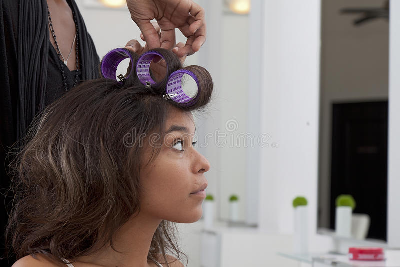 Junge Frau, die Haar sich kräuseln lässt im Schönheitssalon stockfoto