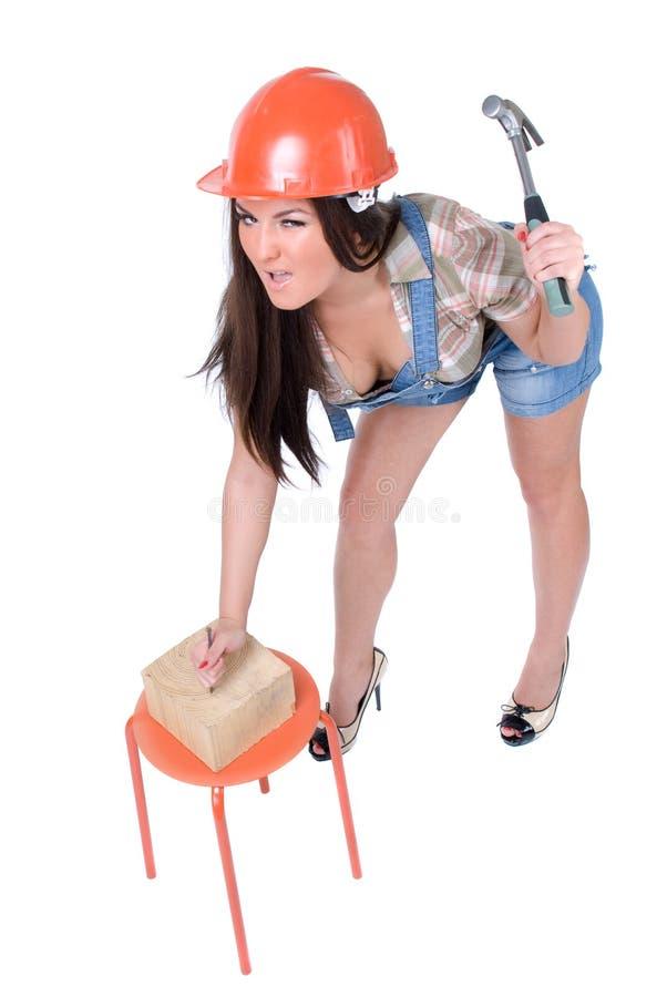 Junge Frau, die Hammer und Nagel hält lizenzfreie stockbilder