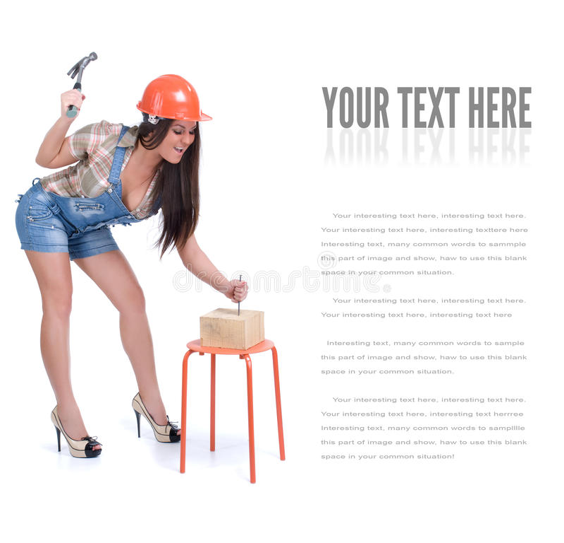 Junge Frau, die Hammer und Nagel hält lizenzfreie stockfotografie