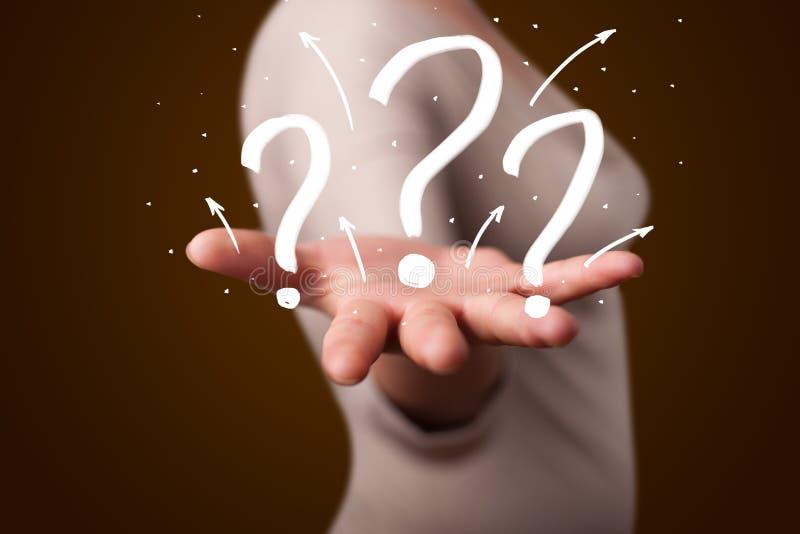 Junge Frau, die Hand gezeichnete Fragezeichen darstellt stockfoto