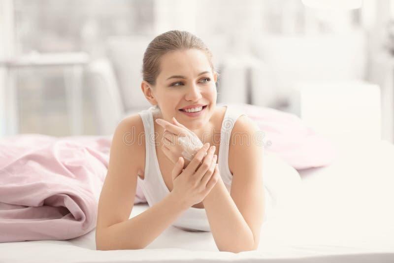 Junge Frau, die Handcreme auf Bett aufträgt lizenzfreie stockbilder