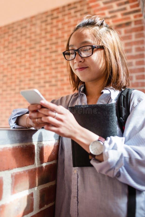 Junge Frau, die Handy im Korridor verwendet stockbild