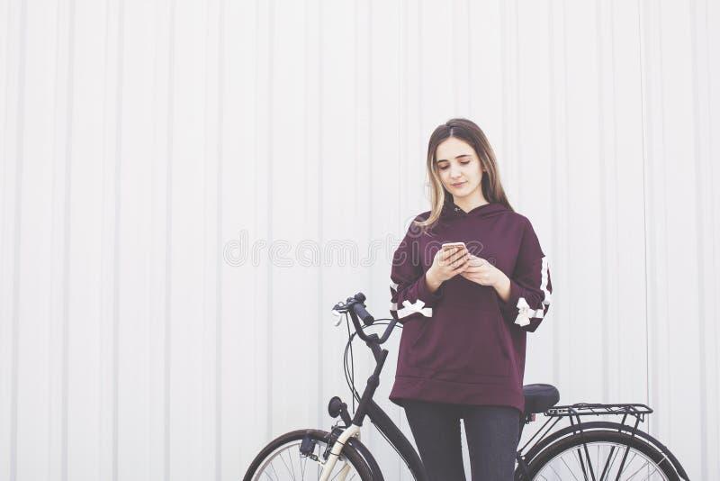 Junge Frau, die Handy nahe bei dem Fahrrad steht auf Wandhintergrund verwendet stockfotos