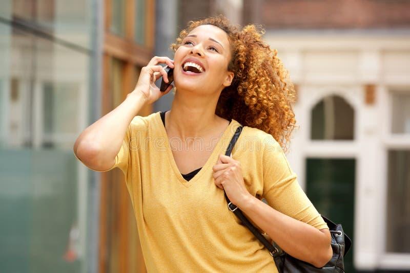 Junge Frau, die am Handy spricht und in der Stadt lacht stockbild