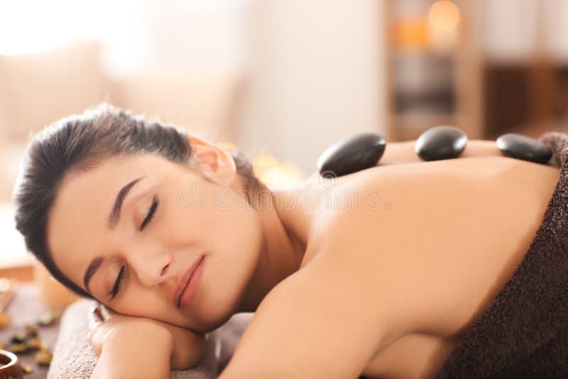 Junge Frau, die heiße Steintherapie auf Massagetabelle am Badekurortsalon durchmacht lizenzfreie stockfotos