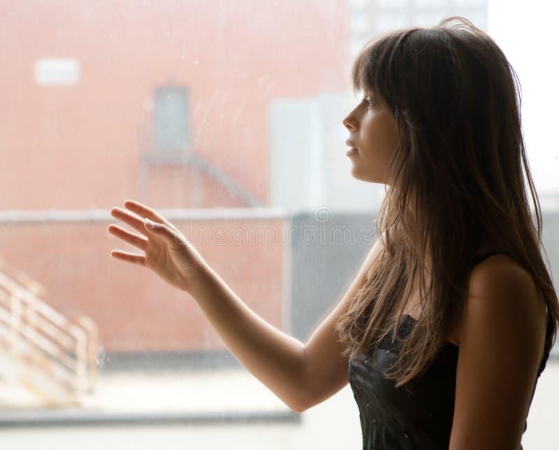 Junge Frau, die heraus großes Fenster anstarrt lizenzfreie stockbilder