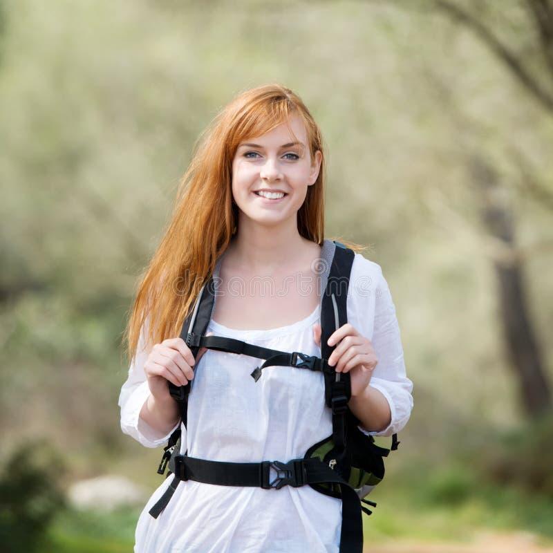 Junge Frau, die heraus mit einem Rucksack wandert lizenzfreie stockbilder