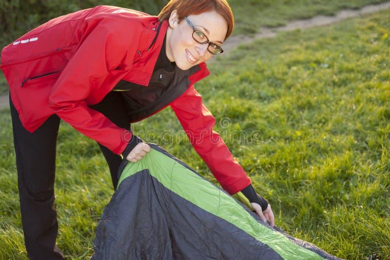 Junge Frau, die heraus Schlafsack von der Abdeckung setzt lizenzfreie stockfotos