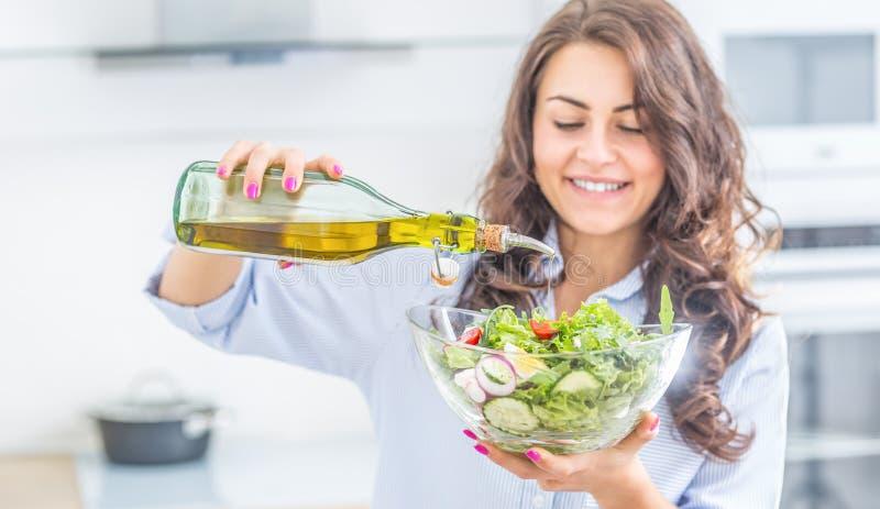 Junge Frau, die herein Olivenöl zum Salat gießt Gesundes Lebensstilessenkonzept lizenzfreie stockfotos