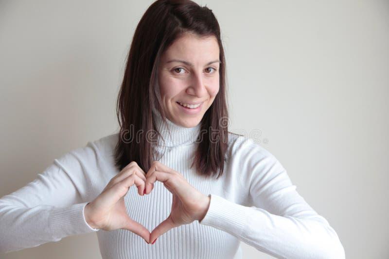 Junge Frau, die Herzsymbol mit den Händen macht stockfotografie