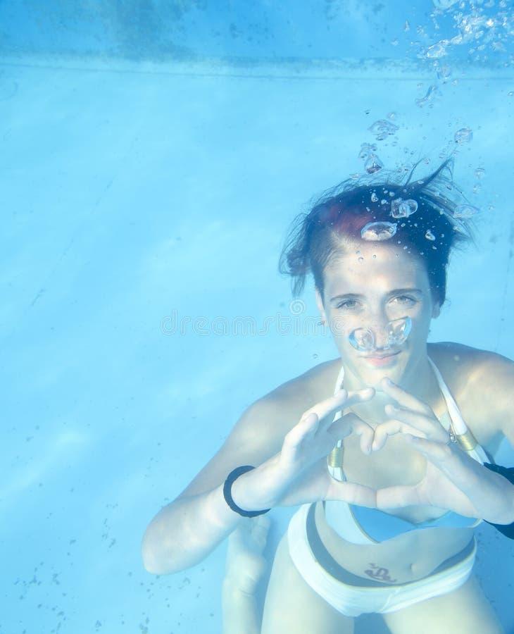 Junge Frau, die Herzsymbol mit ihren Händen Unterwasser macht lizenzfreies stockfoto