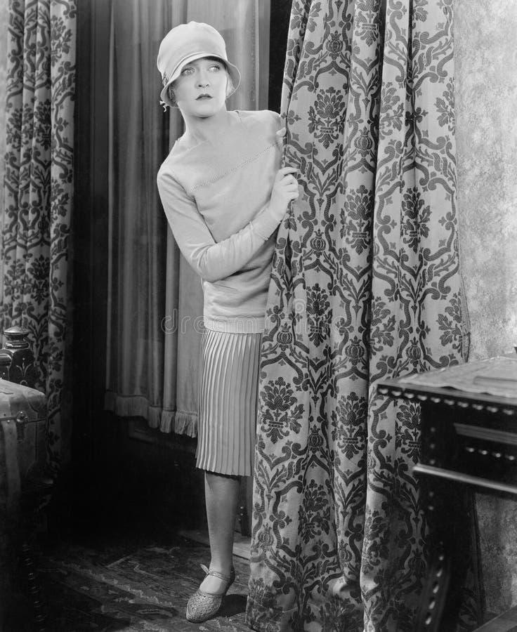 Junge Frau, die hinter einem Vorhang überrascht schaut (alle dargestellten Personen sind nicht längeres lebendes und kein Zustand lizenzfreies stockfoto