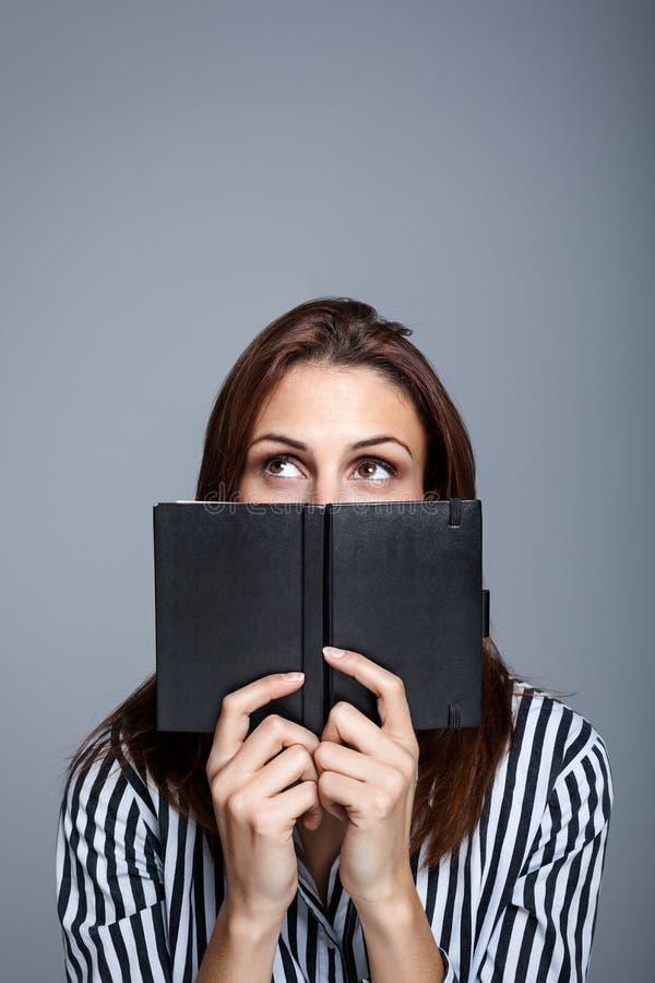 Junge Frau, die hinter ihrem Tagebuch denkt stockfotos