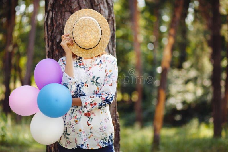 Junge Frau, die hinter Strohhut mit bunten Luftballonen auf Natur sich versteckt stockfotos