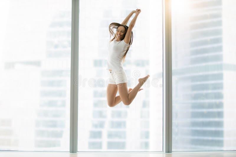 Junge Frau, die hoch springt stockfotos